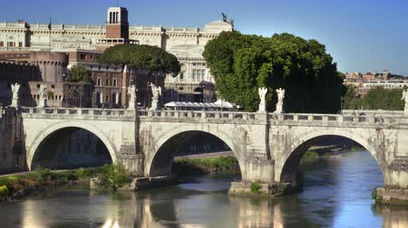 corte : View of Ponte SantAngelo from across the Tiber River. People can be seen crossing it as Corte di Cassazione stands int he background. Shot on May 5,2012 in Rome,Italy Stock Footage