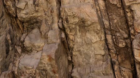 rachaduras : Tracking shot of a rough, vertical rock face.
