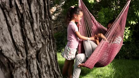 konuksever : Tracking shot of an Asian woman in a pink hammock talking to a little girl. Stok Video