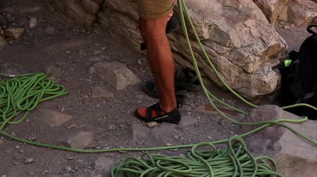 bouldering : Tilt shot of a male rock-climber preparing his footwear and rope.