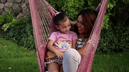 konuksever : An Asian woman and her daughter snuggle together in a pink hammock.