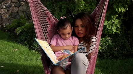 konuksever : An Asian woman and her daughter snuggle together and read a book together in a pink hammock.