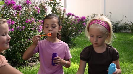 Tracking shot of three little girls blowing bubbles in a garden.