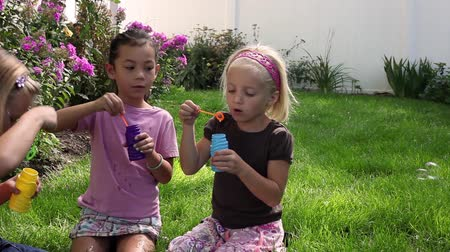 Tracking shot of three little girls blowing bubbles while sitting in a garden.
