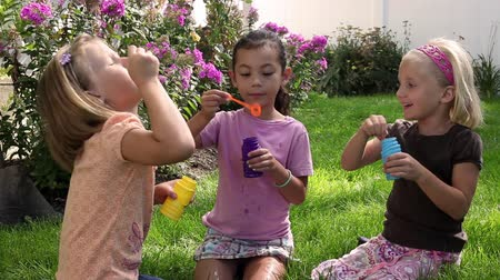 Tracking shot of three little girls blowing bubbles while sitting in a backyard.