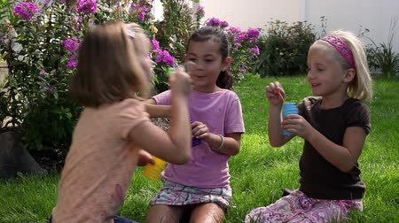 Tracking shot of three little girls blowing bubbles while sitting in a backyards garden.