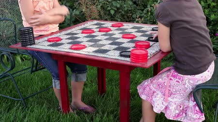 Tilt shot of two little barefoot girls playing a large checker board, Stock Footage