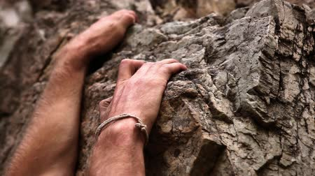 bouldering : Closeup shot of a muscular mans arms searching for a grip while rock-climbing.