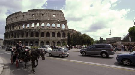 cavalo vapor : A horse drawn carriage and other automobile and pedestrian traffic with the Colosseum in the background Vídeos
