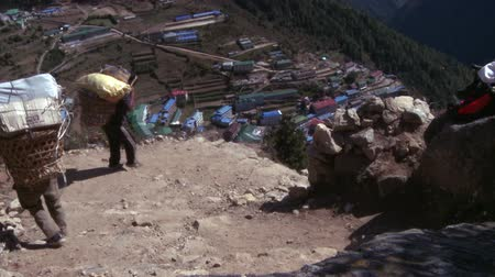 bazar : Two sherpa porters walking down into the village of Namche Bazaar carrying baskets with sacks and supplies.