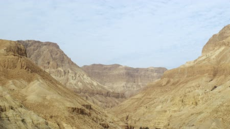 orta : Tilt down to a dry river bed through a desert mountain valley in Israel. Striated clouds in the blue sky oversee the desolate scene. Shot with the Red One digital camera at 4K 4096 x 2304 resolution. 02272011