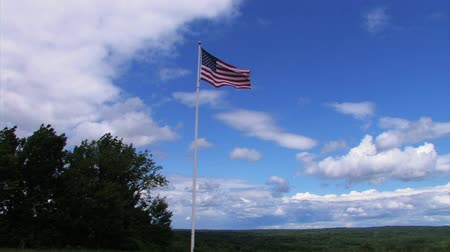 czerwone tło : An American Flag blowing in the wind, with trees below and clouds above.
