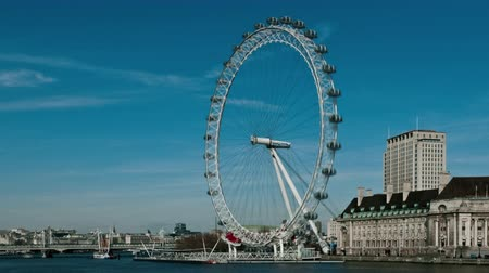 traverse : Time-lapse shot of the London Eye rotating above the Thames. People bustle by in the right corner as boats traverse the water. Filmed in October 2011.