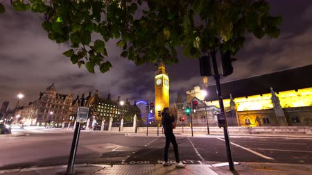 парламент : Time-lapse shot in the evening of Big Ben and Westminster with the London Eye peeking in the background with cars driving down the street in London England. Filmed in October 2011. Стоковые видеозаписи