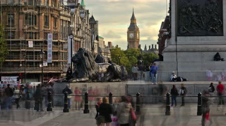 bronz : Time-lapse shot at Trafalgar Square with people all around. There is a statue of a lion and Big Ben off in the distance in London England. Filmed in October 2011.