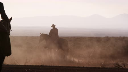 koń : Silhouette shot of a cowboy walking his hourse with dust blowing by. Second cowboy enters