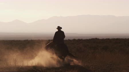 batı : Slow motion silhouette shot of a cowboy riding a hourse in a circle kicking up lots of dust