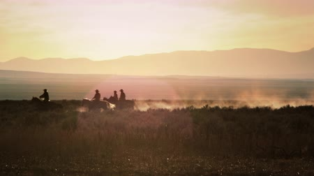 koń : A group of 3 cowboys ride from camera right to camera left leaving a dust trail. Shot in slow motion at sunset