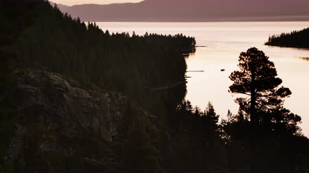 klidný : Static shot of a silhouetted cliff overlooking Lake Tahoe shot a dusk. Shot at Emerald Bay State Park,Lake Tahoe,California