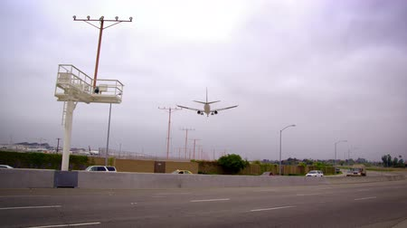 diretamente : Low-angle,slow-motion shot panning to follow an arriving plane as it flies directly overhead. It continues towards the runway,flying over a road full of cars. Filmed at LAX in Los Angeles,California,in June 2012
