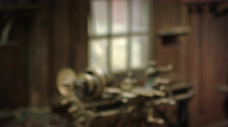 bronz : Racking-focus footage of a strange,small,old-looking machine with cogs standing in a room near a window