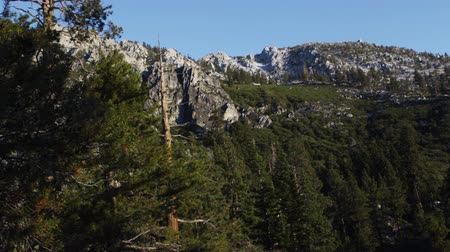 спокойные сцены : Still shot of mountain cliffs. Trees are visible in the foreground. Shot during the day at Emerald Bay State Park,Lake Tahoe,California