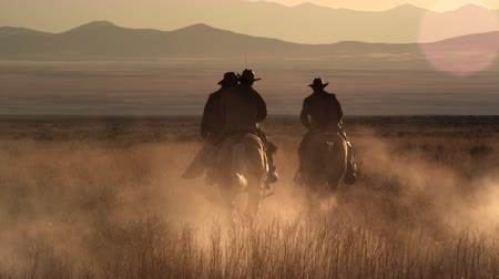 égua : Dusk shot of four cowboys riding off into the sunset towards mountins in the background. They leave a trail of dust behind them