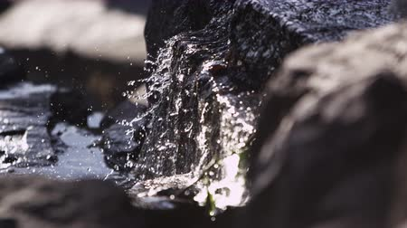 kapatmak : Close-up slow motion shot of water cascading over rocks. This shot was taken during the day and was filmed with a high speed camera. Shot at Emerald Bay State Park Lake Tahoe California. Stok Video