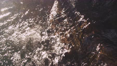 ток : Slow motion shot of water flowing over rocks with a slight glare on the water