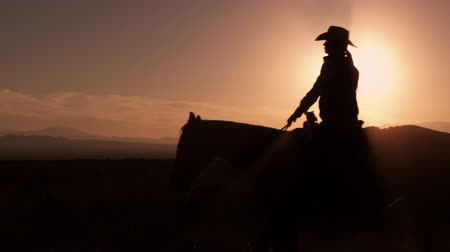 koń : Beautiful silhouette shot of cowboy galloping in front of sunrise. Shot in slow motion Wideo