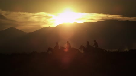 égua : Silhouetted cowboys riding at sunset kicking up dust. Shot in slow motion. Desert landscape with a lens flare.