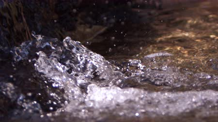 gotas : Still shot of water splashing over rock. Slow motion.