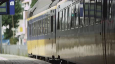 идущий : Static shot of train closing its doors and leaving the train station in Amsterdam. This was taken while the videographer was on the stations platform