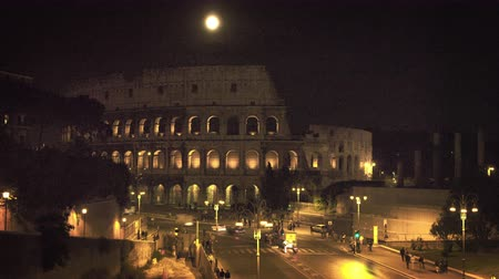 arch of constantine : Footage of a busy intersection near the Colosseum. The Forum is illuminated for the night,and a full moon hangs in the dark sky. Filmed in Rome,Italy on May 6,2012 Stock Footage