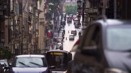 macskaköves : Slow motion footage of a two-way street in which italians touting umbrellas walk and cars pass by. Shot with a high speed camera on May 7,2012 in Rome,Italy