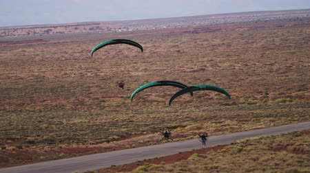 ambição : Panning shot of three powered paragliders. They are coming in for landing over a paved road. Their parachutes are green. Mountains and dessert are visible in the background and surroundings.