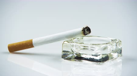 pažba : Close up shot of lit cigarette in an ashtray.