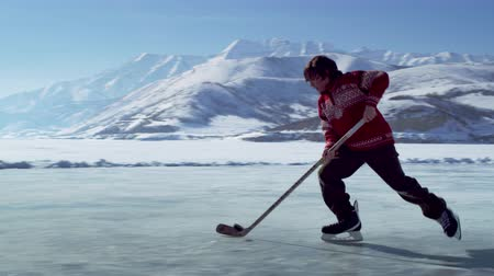 hockey rink : Young boy in a red sweater dribbles a hockey puck a few times back and forth across an outdoor ice rink surrounded by snow capped mountains