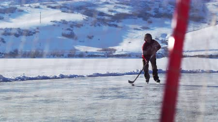 hockey rink : Shot of a young boy through a hockey net as he prepares to dribble forward and score. He is outdoors and surrounded by mountains