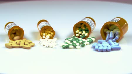 sobre o branco : Assorted pills in bottles on their sides.