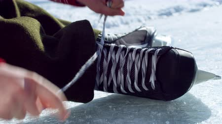skate : A close up shot of a hockey skate on an outdoor ice rink with a quick motion of beginning to tie the laces