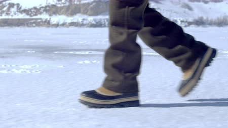 cipőfűző : Snow boots walk across a snow covered ground