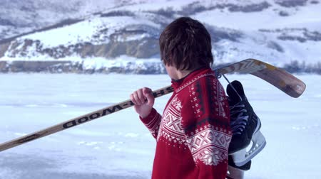 skate : A young boy in a red sweater walking across a snowy field carrying hockey gear over his shoulder with large mountains in the background Stock Footage