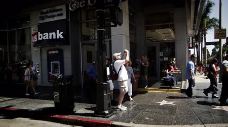 kávézó : Slow motion tracking shot of structures along Hollywood Blvd. in California. The camera passes the US bank along with some people and vehicles in the street. This was taken in June 2012