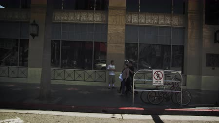suvenýry : Slow motion dolly shot of buildings along Hollywood Blvd. in California. The Coffee Bean and Tea Leaf is seen in the shop along with some people and vehicles in the street. This was taken in June 2012