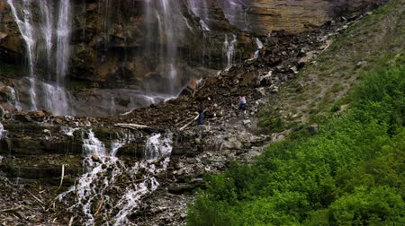 inferior : People on the rocky hillside at the bottom of Bridal Veil Falls in Provo Canyon Utah.