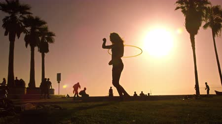 abroncs : Slow motion shot with lens flare of a woman playing with a hula hoop near Venice Beach,California. This was taken at dusk on Ocean Front Walk near Venice Beach,California in June 2012
