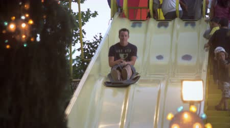 inferior : Slow motion shot of boy riding down a slide at a carnival. He is smiling by the time he gets to the bottom