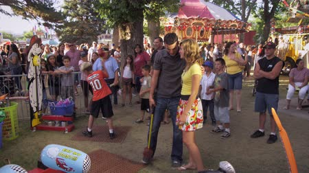 премия : A shot of a man and a girl at a carnival. The man is playing the hammer game,and the girl is standing beside him