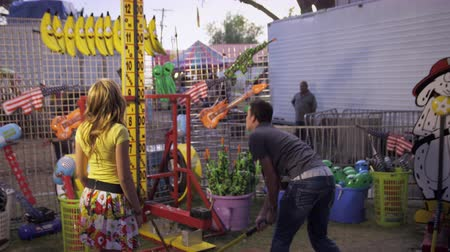 martelo : A shot of a man swinging a hammer at a carnival game. He is accompanied by a girl who hugs him after he swings Stock Footage